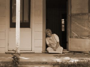 Woman sits in the doorway of her condemned house.