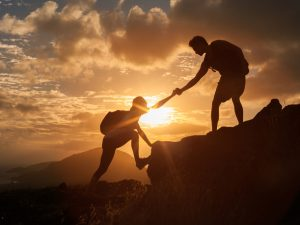 Male and female hikers climbing up mountain cliff and one of them giving helping hand. People helping and team work concept.