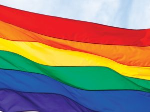 Gay Rainbow Flag isolated on white and blue sky background.