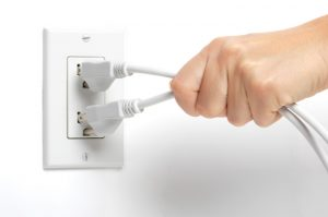 woman unplugging electrical cords on white