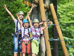 Little girl aged 10 with her brothers aged 7, wearing helmets stadning on wooden platform holding zip line in the outdoors ropes course adventure park. Kids are smiling at the camera and cheering.