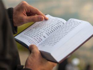 Uman, Ukraine - September 15, 2015: Man holding Mahzor - prayer book used by Jews on the High Holidays of Rosh Hashanah and Yom Kippur.