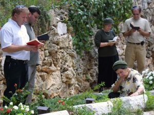 Jerusalem, Israel - September 30, 2001: Israelis pray at a memorial service at the Mount Herzl Military Cemetery two days after the first anniversary of the Second Intifada. A visit by Ariel Sharon to the Temple Mount, or Noble Sanctuary, triggered the Second Intifada.