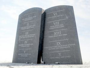 Two stone tablets with the ten commandments inscribed on them standing in brown desert sand infront of a blue sky - 3D render