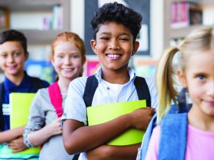 Portrait of a happy multiethnic children holding books and wearing backpack at primary school. Schoolboys and cute girls in a row holding notebook and looking at camera. Portrait of a elementary child smiling.