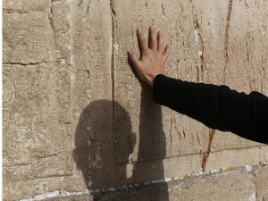 Hand and shadow of praying man on the stones of the ancient Western wall in the old city of Jerusalem, Israel.