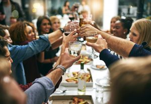 Cropped shot of a group of young friends toasting during a dinner party at a restaurant