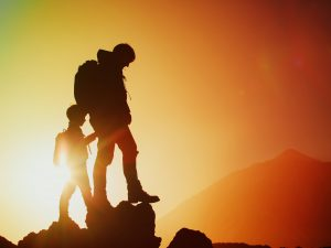 Silhouettes of father and son hiking in mountains at sunset, travel concept
