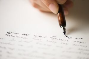 Writing letter to a friend. Selective focus and shallow depth of field.