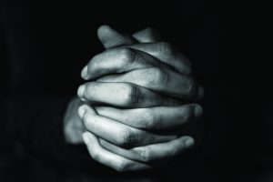 closeup of the hands of a young caucasian man with his hands clasped, in black and white